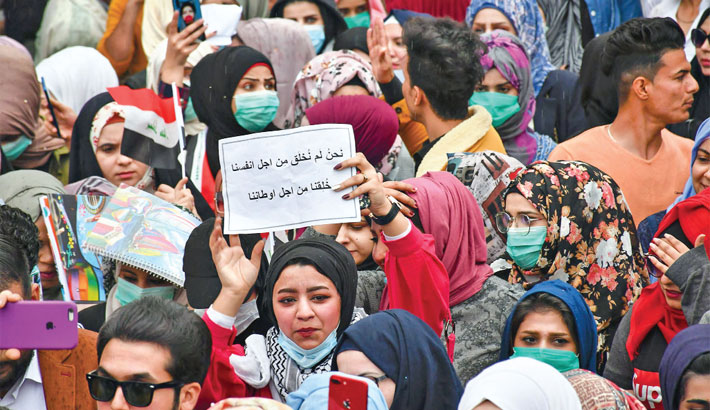 Iraqi students take part in an anti-government march calling