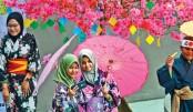 Visitors wearing kimonos take selfies