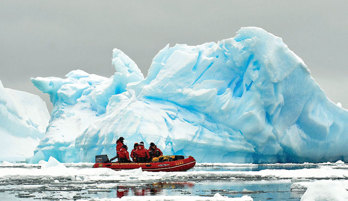 Expeditioners cruise past icebergs in an inflatable boat near the ADD's Mawson Station in Antarctica