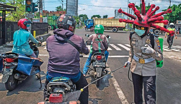Indonesian police officer wearing a Covid-19 coronavirus themed helmet
