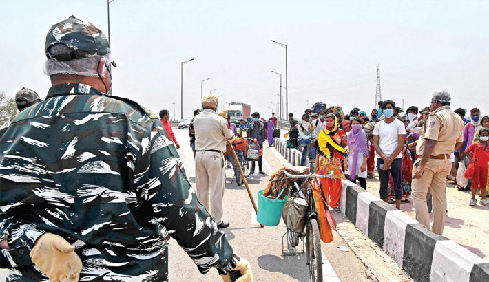 Indian security personnel stop migrant workers