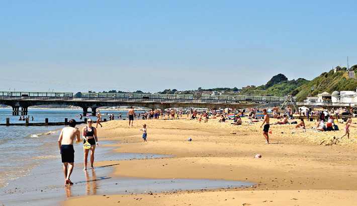 People observe social distancing as they enjoy the sunshine on the beach