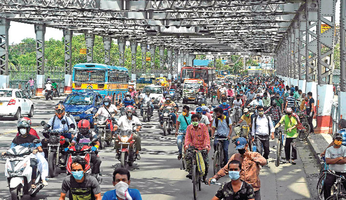Commuters ride bicycles along the Howrah Bridge to go to work