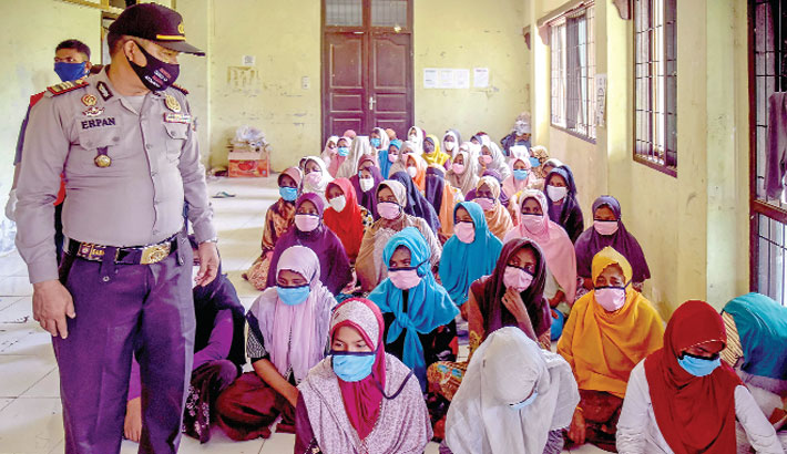 An Indonesian policeman stands next to Rohingya women