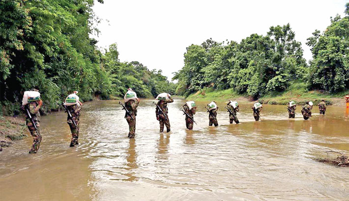 Bangladesh Army carry food items for the poor