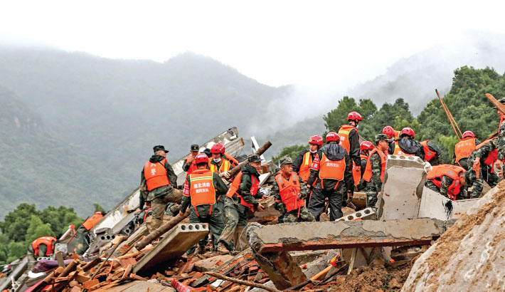 Rescuers working at the scene of a landslide in Huangmei county