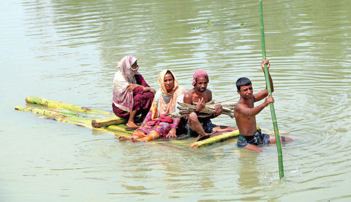 Flood-affected people move to a safe place by a raft in Balasi area