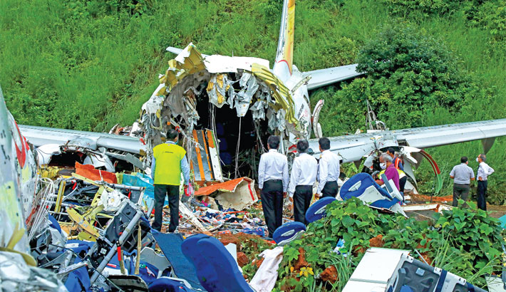 Officials inspect the wreckage of an Air India Express jet at Calicut International Airport in Karipur, Kerala