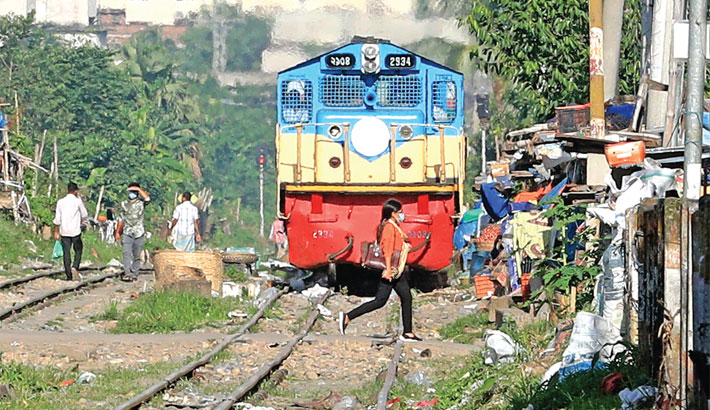 A woman is crossing a railway track, risking her life