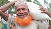 Elderly man carries a sack of relief items