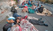 Refugees and migrants sit on the road as they wake up after a fire destroyed Greece's largest Moria refugee camp