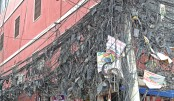 Internet and TV cables are hanging from an electrical pole