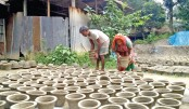 Artisans are seen busy drying earthen pots