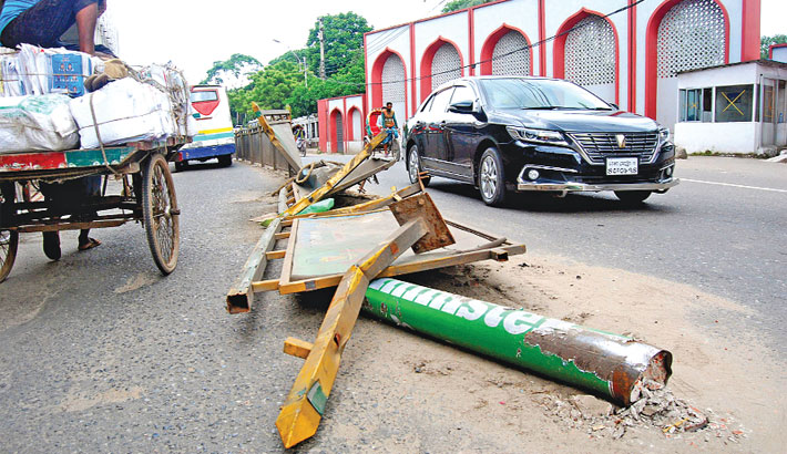 Damaged road dividers lie on a busy road
