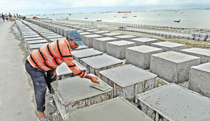Worker is making concrete blocks