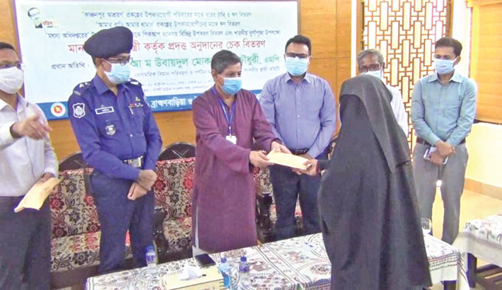 Hands over financial assistance cheque to poor people