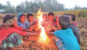 A group of children huddle together by the fire to protect themselves from cold