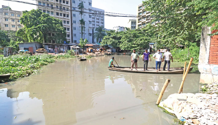 Commuters cross a water body by a boat near Bangladesh Bank
