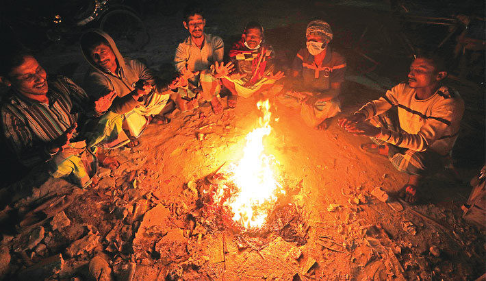 Day labourers light a fire and huddle around it to protect themselves from the cold