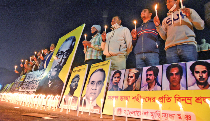 Activists of Bangladesh Muktijoddha Moncho light candles at  the base of Raju Sculpture