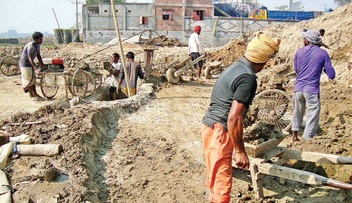 Workers of a brick kiln are busy preparing earth pulp to make bricks