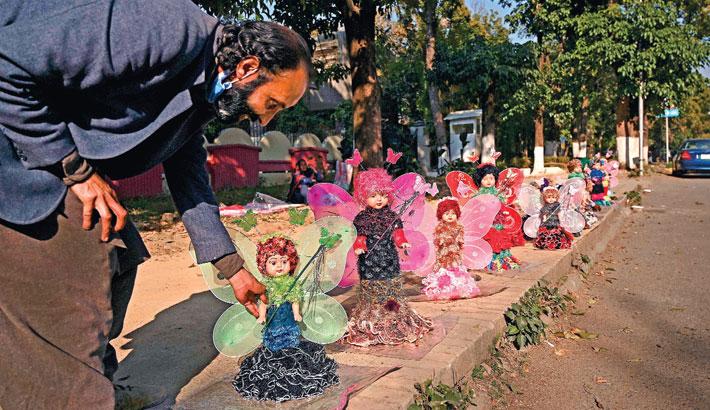 A roadside vendor adjusts a doll kept for sale