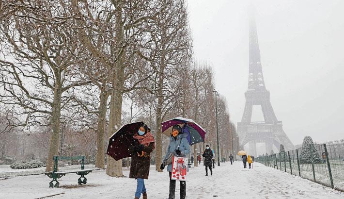 People walk with umbrellas in Champ de Mars park