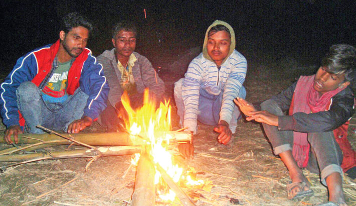 A group of day labourers light a fire