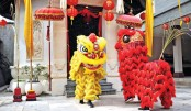 Lion dancers stand outside a temple on the first day