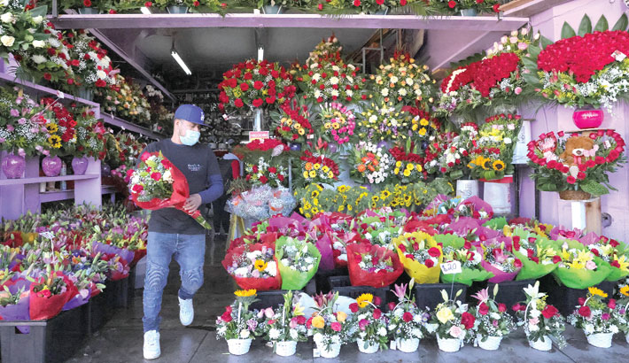 A worker carries a bouquet in the flower district on Valentine's Day
