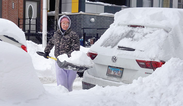 Michaela Quan digs out her car after it was buried in snow