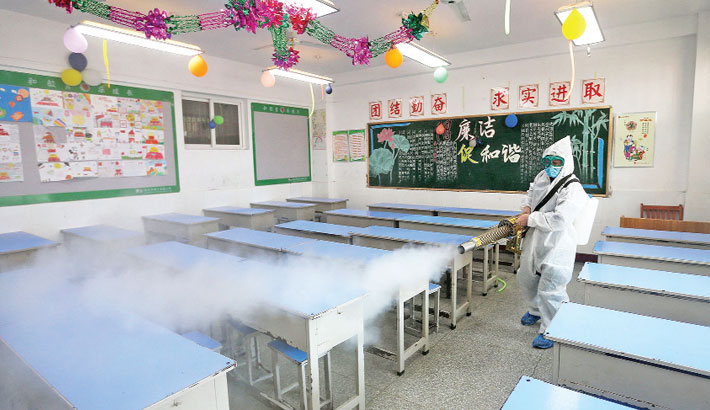 A worker sprays disinfectant in a classroom