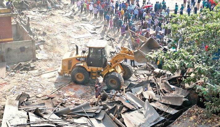 A bulldozer of Kamalapur district administration removes illegal establishments