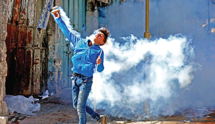 A Palestinian protester throws back a tear gas canister during