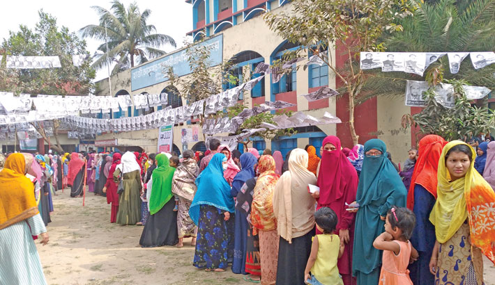 Voters are seen standing in a queue to cast their votes