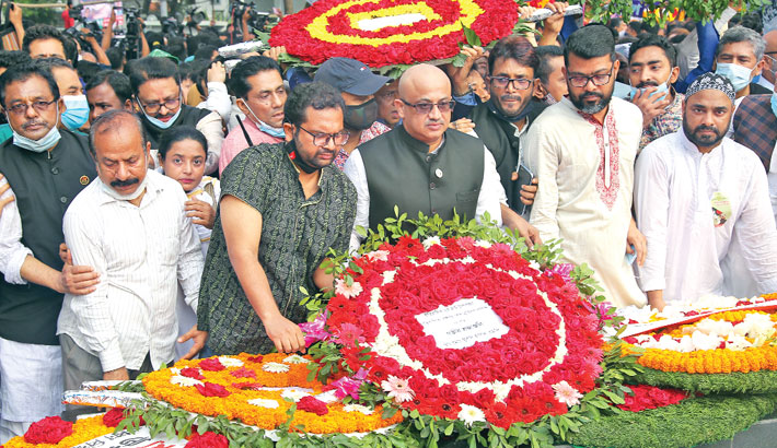State Minister for Information Dr Md. Murad Hassan along with others places a wreath at the portrait