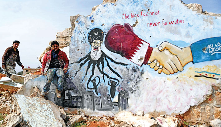 Syrians stand next to a painted mural on the remains of a building depicting Iran