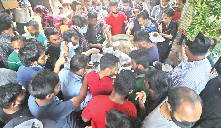 Mohammadpur residents throng a restaurant to collect ready foods