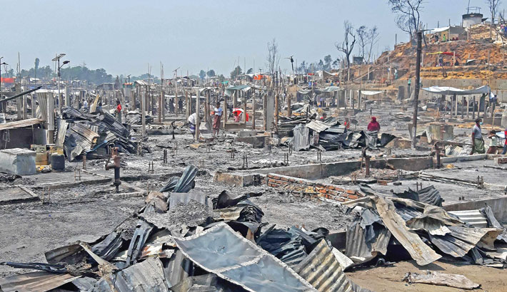 People are seen amidst the debris at a Rohingya camp in Ukhia of Cox's Bazar