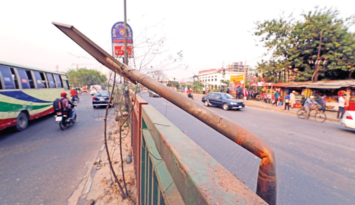 An electric pole beside a road divider has bent dangerously towards the motorway