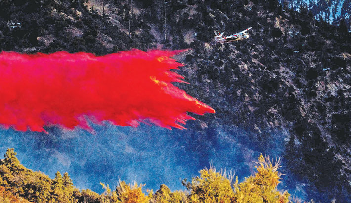 An airplane drops fire retardant on the Springs Fire as it burns along