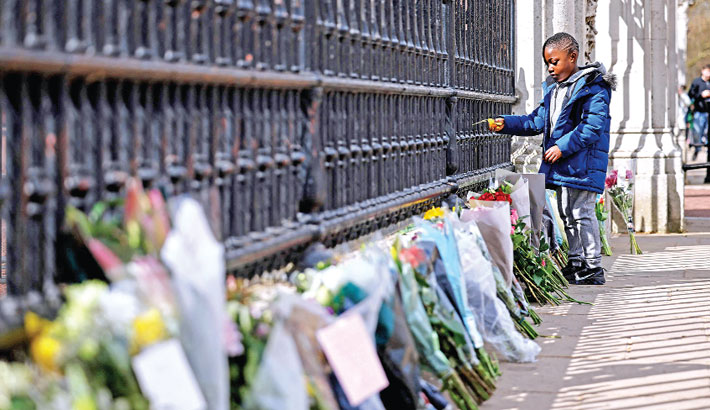 A boy adds to floral tributes against the railings