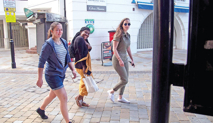 Young women without protective face masks walk down a street in Gibraltar