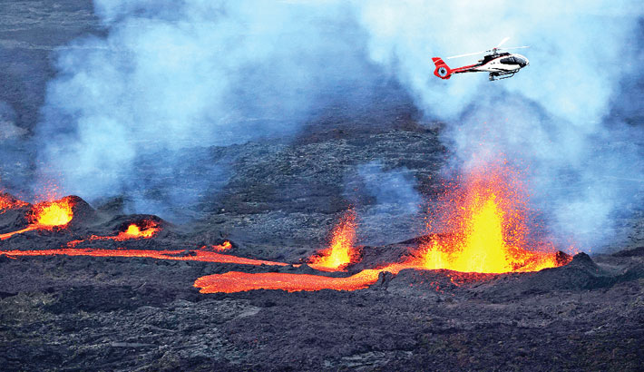 A helicopter flying as lava is erupting from Piton de la Fournaise volcano