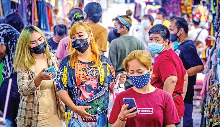 People wearing protective face masks shop at Pratunam market in Bangkok on Friday