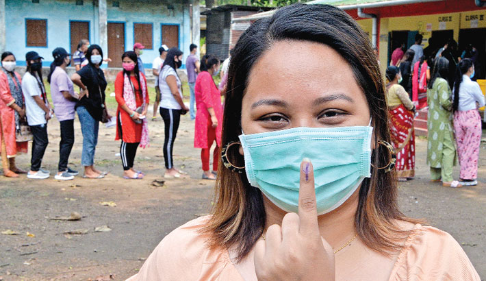 A voter shows her inked finger after casting her ballot as others stand
