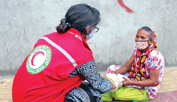 Bangladesh Red Crescent Society (BDRCS) hands over a box of cooked food to a poor woman