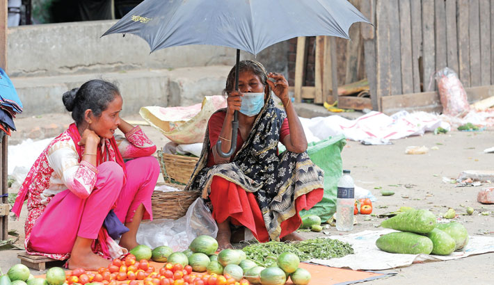 Two women wait for buyers after displaying their vegetables for sale