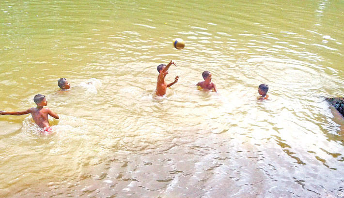 Some boys are taking fun bath in a pond amid the scorching summer heat