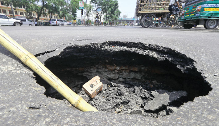 A bamboo pole jutting out of a subsided section of a busy road in the capital's GPO intersection